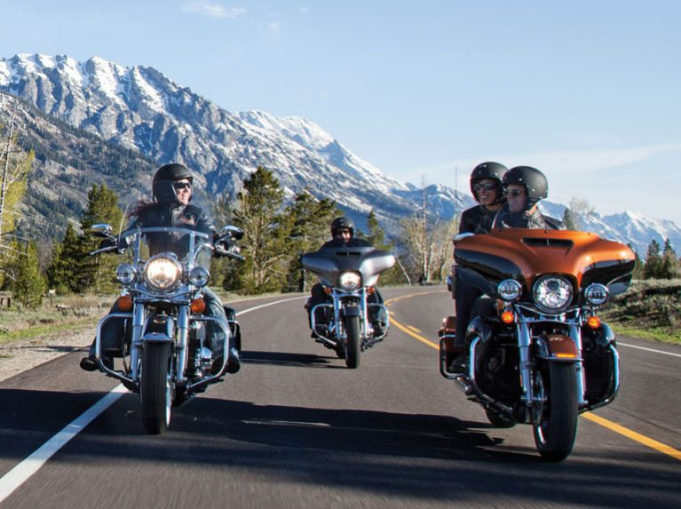 A group of Harley-Davidson riders, with Dunlop tyres riding on the open road
